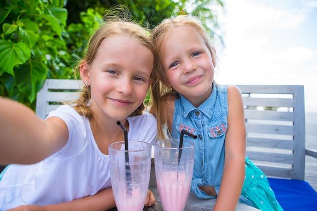 Kleine mädchen, die selfie nehmen und geschmackvolle cocktails am tropischen erholungsort trinken