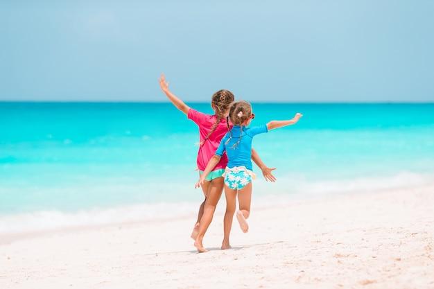 Kleine mädchen, die spaß am tropischen strand haben, der zusammen am flachen wasser spielt
