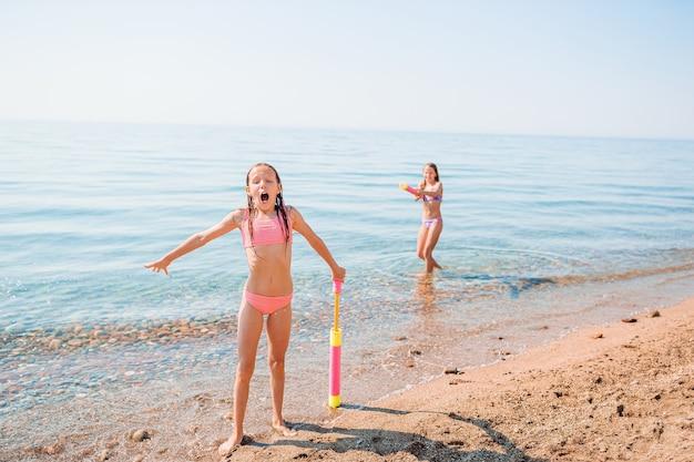 Kleine mädchen, die spaß am tropischen strand während der sommerferien haben, die zusammen spielen