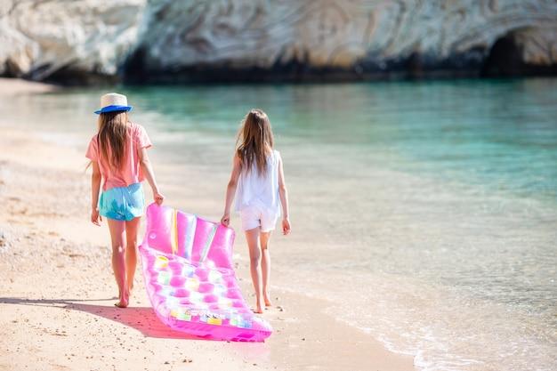 Kleine mädchen, die spaß am tropischen strand während der sommerferien zusammen spielen haben