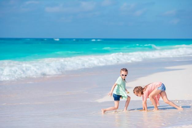 Kleine mädchen, die spaß am tropischen strand zusammen spielt am seichten wasser haben