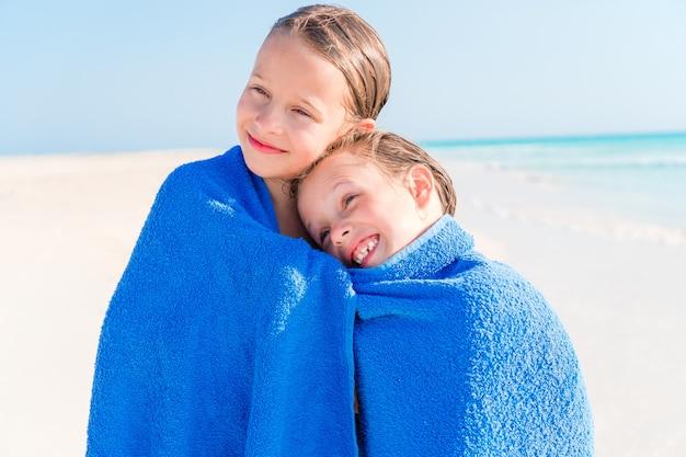 Kleine mädchen, die spaß haben, mit handtuch laufen und urlaub am tropischen strand mit weißem sand und türkisfarbenem meerwasser genießen