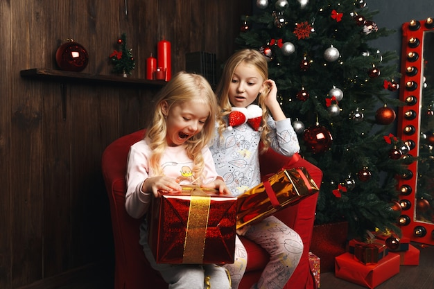 Kleine mädchen, die weihnachtsgeschenke öffnen