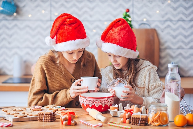 Kleine mädchen, die weihnachtslebkuchen kochen. backen und kochen mit kindern zu weihnachten zu hause.