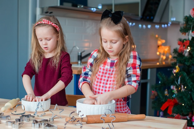 Kleine mädchen, die weihnachtslebkuchenhaus am kamin in verziertem wohnzimmer machen.