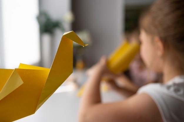Kleine mädchen, die zu hause mit origami-papier spielen