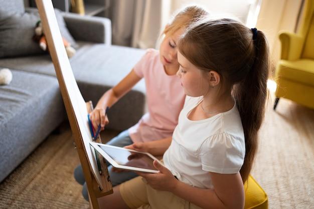 Kleine mädchen, die zu hause mit staffelei und tablet zeichnen