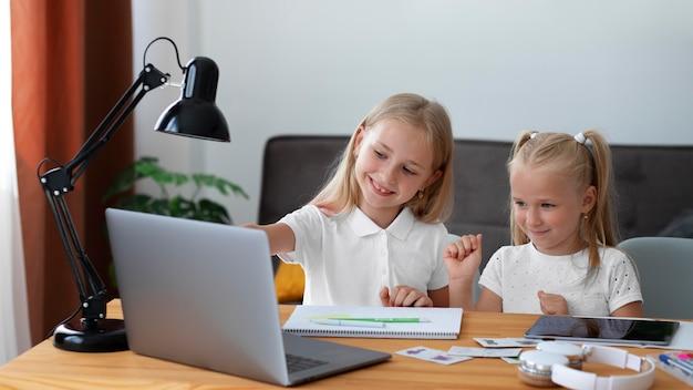 Kleine mädchen, die zu hause zusammen online-schule machen