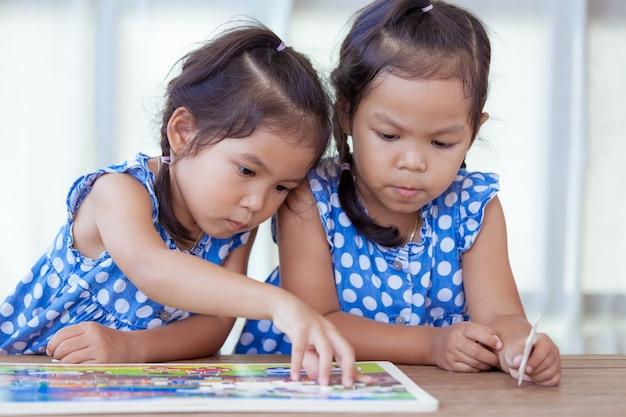 Kleine mädchen, die zusammen ein puzzlespiel machen