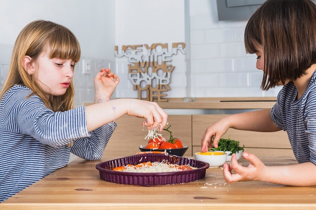 Kleine mädchen, die zusammen hausgemachte pizza in der küche kochen