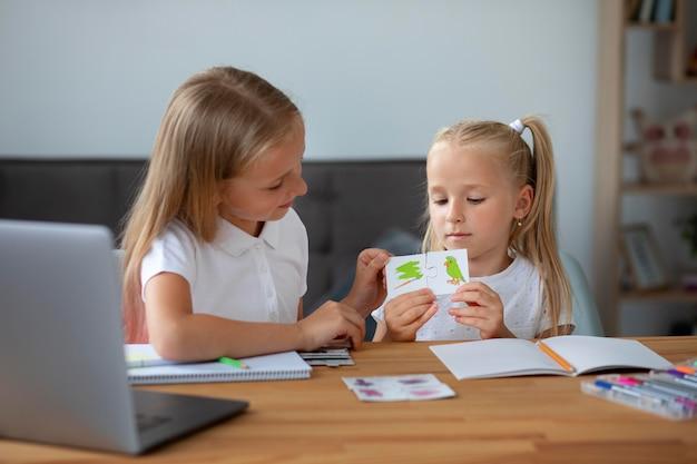 Kleine mädchen, die zusammen online-schule machen
