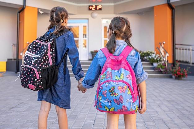 Kleine mädchen, grundschüler, gehen mit rucksäcken zur schule und halten sich an den händen.