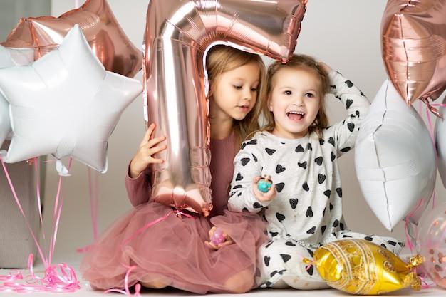Kleine mädchen im abendkleid, das aus einem ballon in form sieben heraus schaut