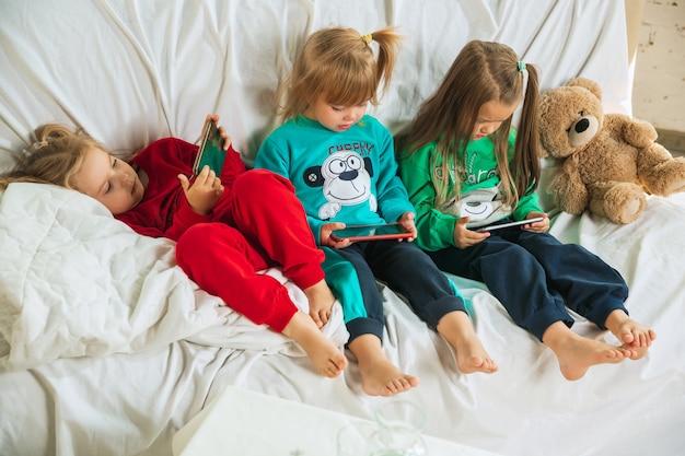 Kleine mädchen im weichen warmen pyjama, der zu hause spielt. kaukasische kinder in bunten kleidern, die spaß zusammen haben. kindheit, häuslicher komfort, glück. auf dem sofa liegen und das smartphone für das spiel verwenden.