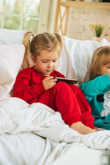 Kleine mädchen im weichen warmen pyjama, der zu hause spielt. kaukasische kinder in bunten kleidern, die spaß zusammen haben.