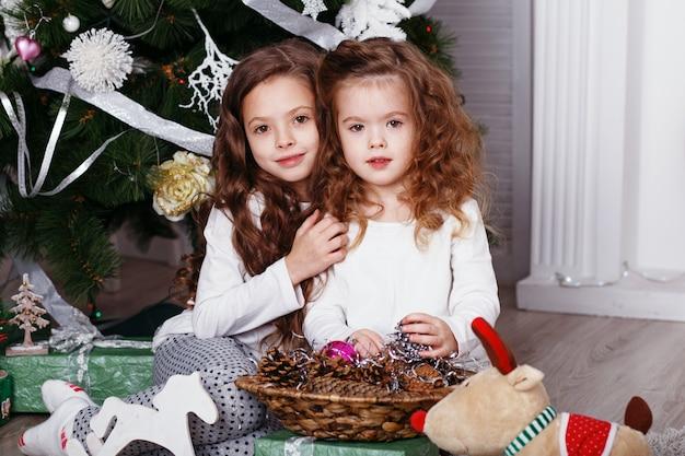 Kleine mädchen in bequemer hauskleidung, die auf boden in schönen weihnachtsdekorationen sitzt