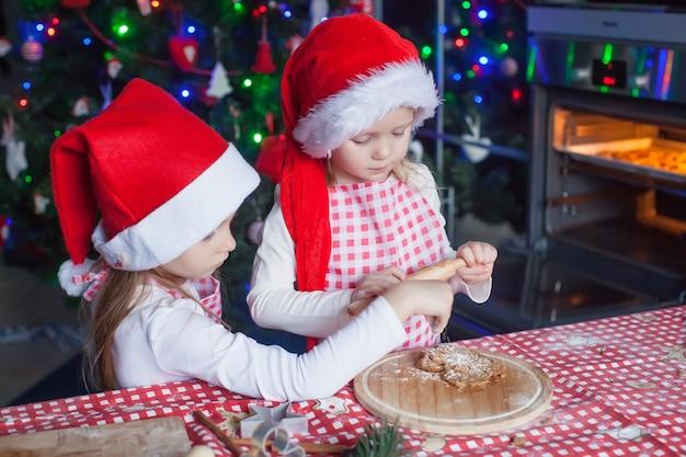 Kleine mädchen in sankt-hüten, die weihnachtslebkuchenplätzchen backen