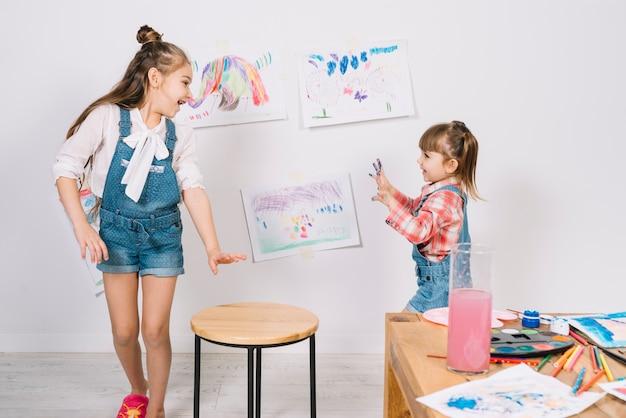 Kleine mädchen laufen mit gemalten fingern