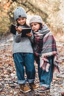 Kleine mädchen lesen an einem herbsttag ein buch. entwicklung, bildung, schule. ein