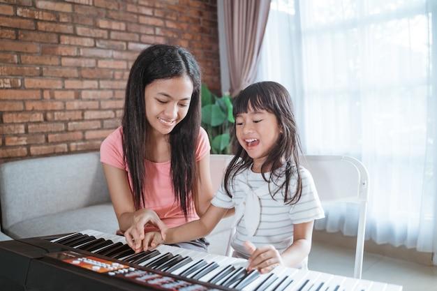 Kleine mädchen mit einem lächeln spielen eine musikinstrumententastatur