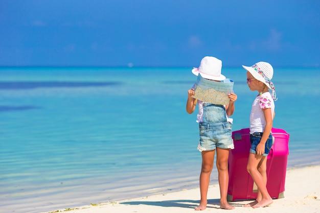 Kleine mädchen mit großem koffer und karte am tropischen strand