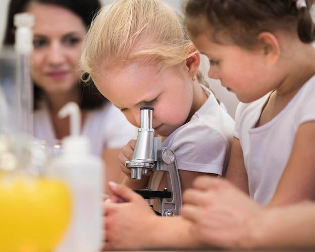 Kleine mädchen mit mikroskop
