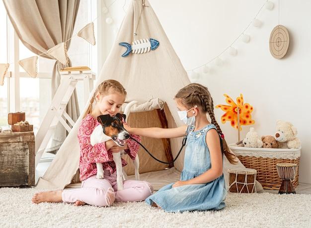 Kleine mädchen mit phonendoskop hörendem hund wie doktor, der auf boden im spielzimmer sitzt