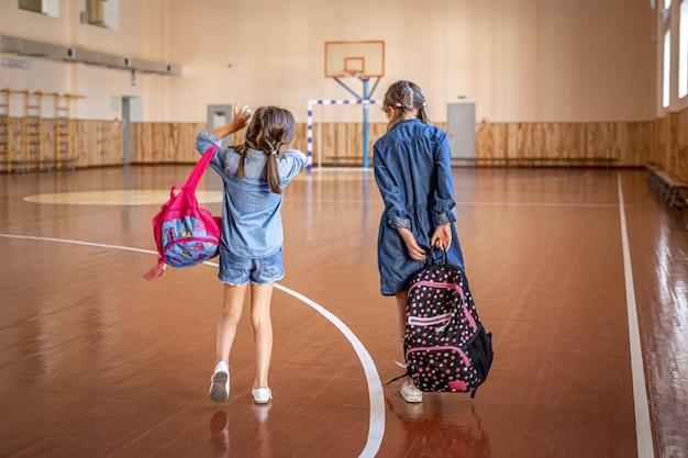 Kleine mädchen mit rucksäcken in einer leeren turnhalle.