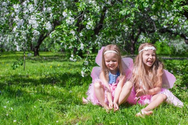 Kleine mädchen mit schmetterlingsflügeln im blühenden apfelgarten