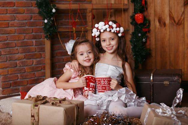 Kleine mädchen mit weihnachtlichen strickbechern