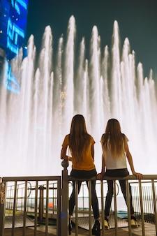 Kleine mädchen sehen sich die legendäre show der springbrunnen in dubai an