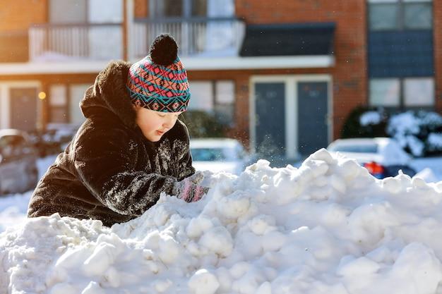 Kleine mädchen spielen draußen am verschneiten wintertag im schnee