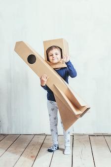 Kleine mädchen spielen raumfahrer mit einer papprakete und einem papphelm