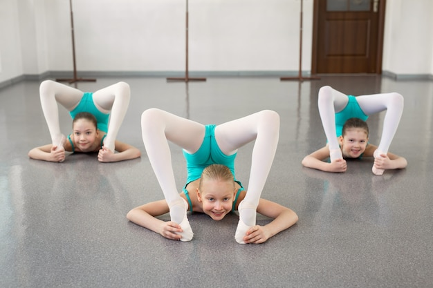 Kleine mädchen tanzen ballett im studio. junge ballerinas, die sich vor der aufführung dehnen, klassische tanzschule