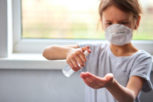 Kleine mädchen tragen hygienemaske und drücken alkoholspray zum schutz, desinfektion. coronavirus-, covid-19- und umweltschutzkonzept. bleib zuhause.