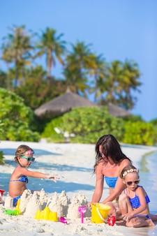 Kleine mädchen und glückliche mutter, die mit strandspielwaren auf sommerferien spielt
