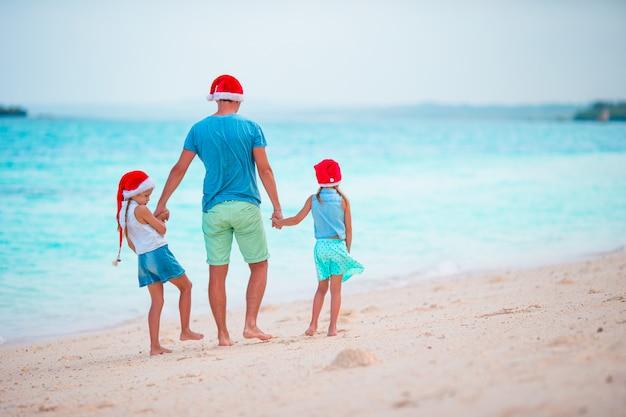 Kleine mädchen und junger vater in santa hats genießen weihnachtsferien