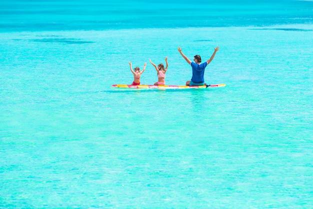 Kleine mädchen und junger vati auf surfbrett während der sommerferien