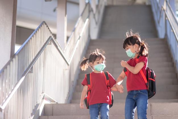 Kleine mädchen und schwestern in schutzmasken mit schulrucksäcken. blick auf grundschüler, die eine schultasche tragen.