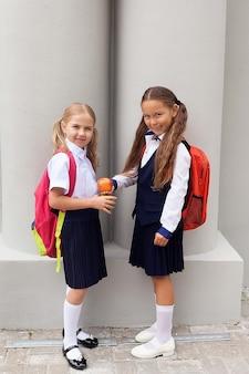 Kleine mädchen von 6-7 jahren halten im freien einen frischen apfel in den händen. in schulrucksack und uniform. kindheit. zurück zur schule. 1. september. guten morgen.