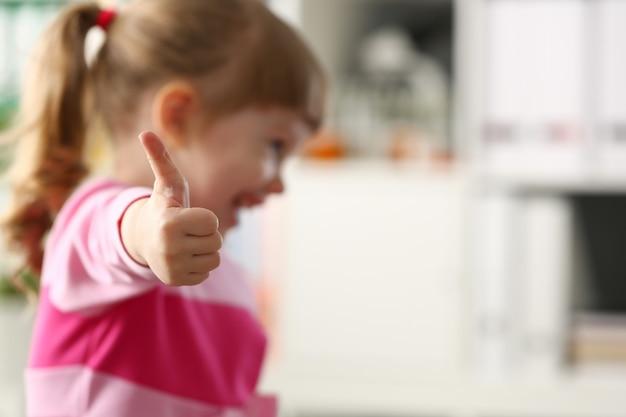 Kleine mädchen zeigen genehmigen oder ok unterschreiben mit ihrem arm