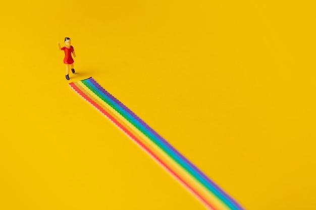 Kleine mädchenfigur auf dem lgbt-regenbogenweg