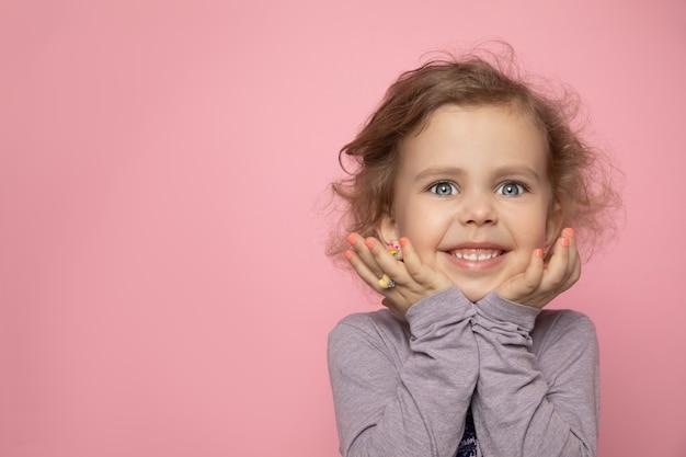 Kleine mädchenkindblondine mit lockigem mädchen malte ihre finger mit nagellack, schaute in den rahmen im studio und lächelte.