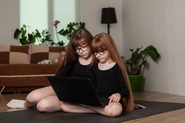 Kleine mädchenschwestern halten eine online-gymnastikstunde zu hause