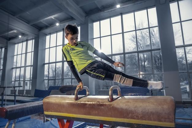Kleine männliche turnerausbildung im fitnessstudio, flexibel und aktiv