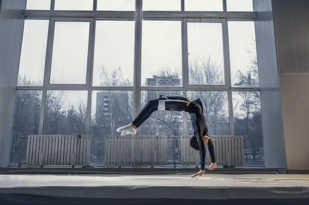 Kleine männliche turnerin trainiert im fitnessstudio flexibel und aktiv