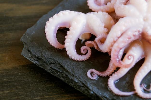 Kleine marinierte kraken auf schwarzem hintergrund.