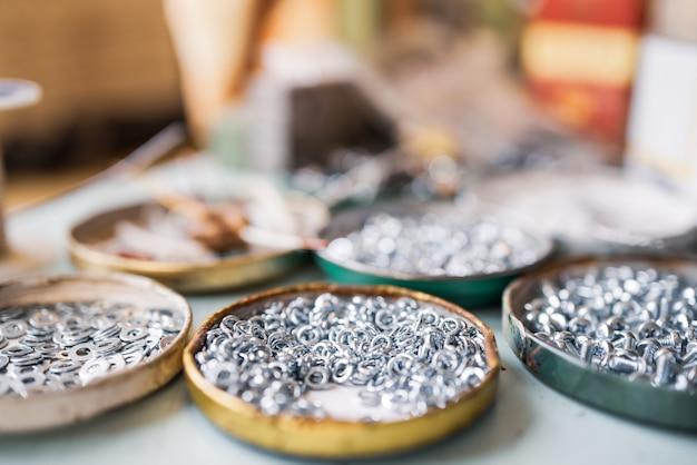 Kleine metallmuttern und ein schraubenschlüssel liegen in chaotischer reihenfolge auf dem arbeitstisch des monteurs. hintergrundkonzept für verbindungselemente und konstruktionsthemen. reparatur- und ersatzteilkonzept