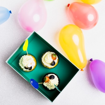 Kleine muffins im grünen kasten mit luftballons