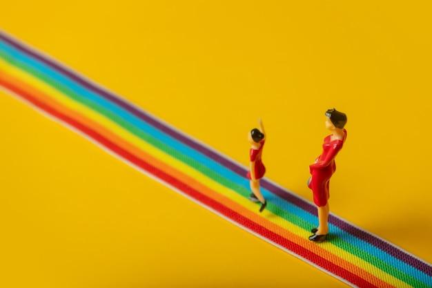 Kleine mutter-tochter-figuren auf dem lgbt-regenbogenweg